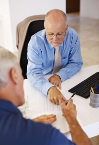 Financial male consultant asking senior man to fill the form at office