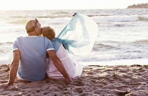 Cash in my Pension - retired couple on beach on holiday with the money they have cashed in from their pension